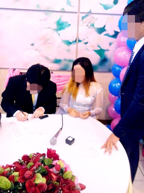フィリピン人女性との結婚式で結婚許可証にサイン